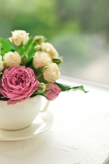 Bouquet of white roses in a cup on a white table opposite the window