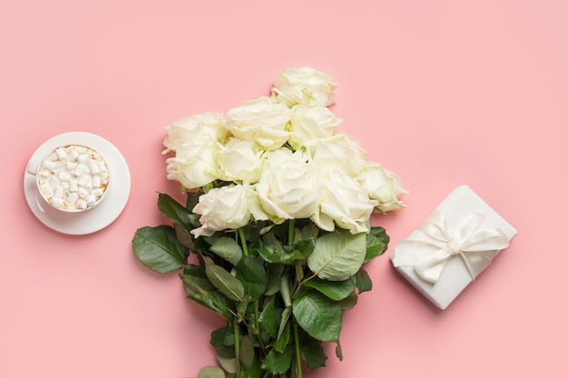 Bouquet of white roses, female gift and cup of coffee on pink. top view, copy space.