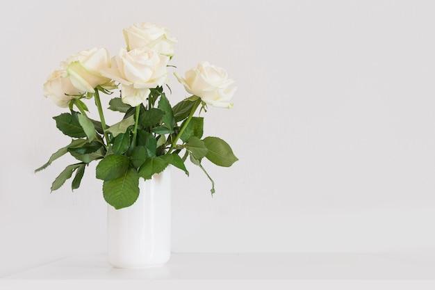 Bouquet of white roses flower in vase on white shelf.