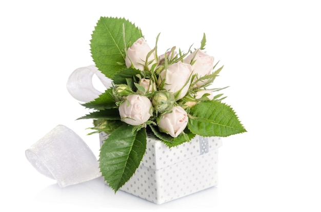 Bouquet of white roses and gift box on white surface