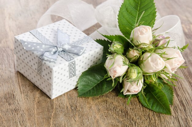 Bouquet of white roses and gift box