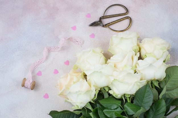 A bouquet of white roses, old scissors, pink hearts and lace ribbon