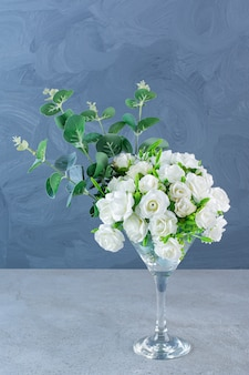Bouquet of white roses with green leaves on glass cocktail glass