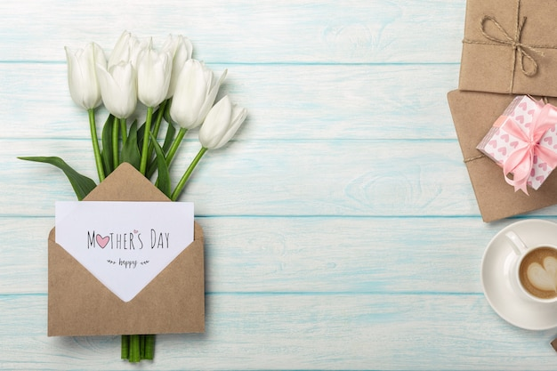 A bouquet of white tulips, cup of coffee, gift box with a love note and envelope on blue wooden boards . mother's day