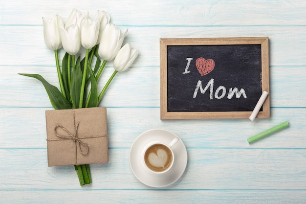 A bouquet of white tulips, cup of coffee with chalk board and envelope on blue wooden boards . mother's day