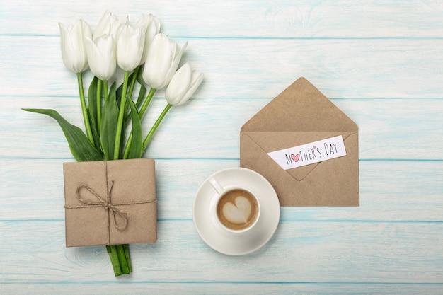 A bouquet of white tulips, cup of coffee with a love note and envelope on blue wooden boards . mother's day