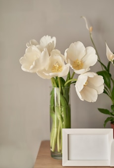 Bouquet of  white tulips and empty photo frames.