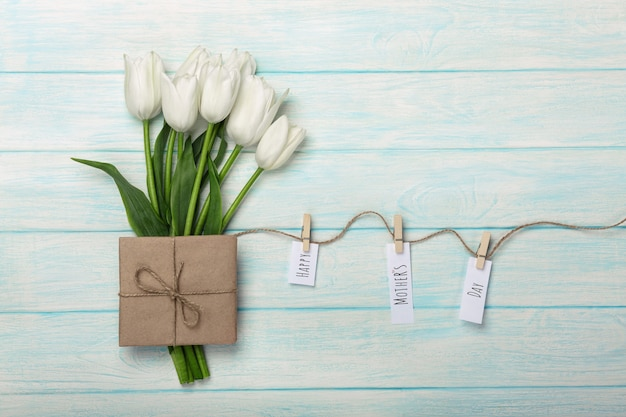 A bouquet of white tulips and envelope with a stickers with clothespins on a rope and blue wooden boards . mother's day