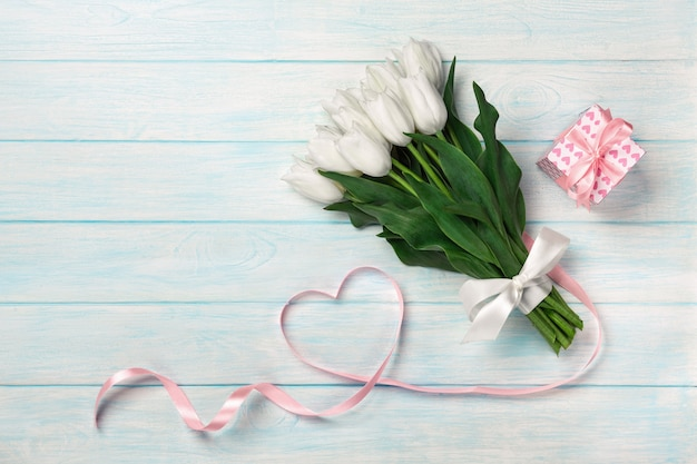 A bouquet of white tulips and a pink ribbon in the form of a heart with a gift box on blue wooden boards .