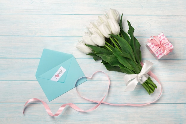 A bouquet of white tulips and a pink ribbon in the form of a heart with a gift box, love note and color envelope on blue wooden boards. mother's day