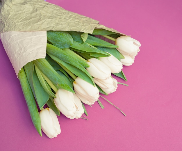 A bouquet of white tulips and a red velvet heart on a pink table - the concept of valentine's day.