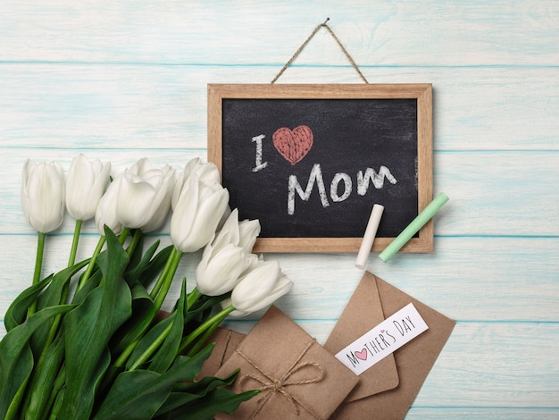 A bouquet of white tulips with chalk board, love note and envelopes on blue wooden boards. mother's day