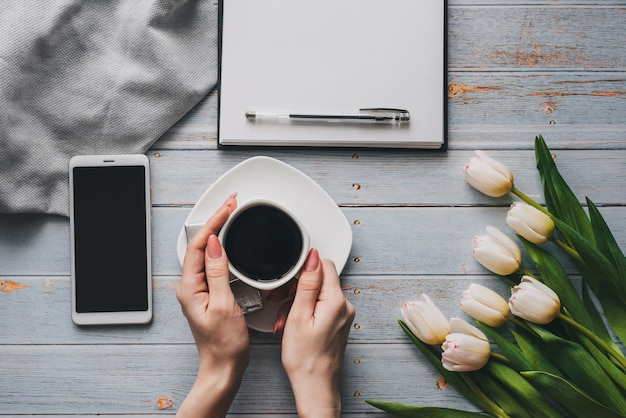 Bouquet of white tulips with a cup of coffee in women's hands, a smartphone and an empty notebook for text
