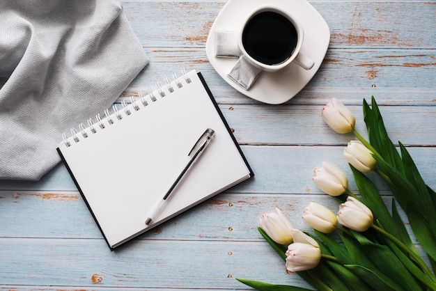 Bouquet of white tulips with an empty notebook, a cup of coffee on a wooden background