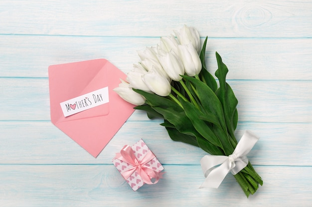 A bouquet of white tulips with a gift box, love note and color envelope on blue wooden boards. mother's day