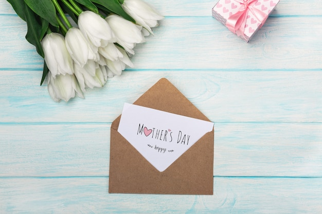 A bouquet of white tulips with a gift box, love note and envelope on blue wooden boards . mother's day