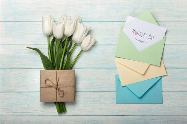 A bouquet of white tulips with a love note and color envelopes on blue wooden boards . mother's day