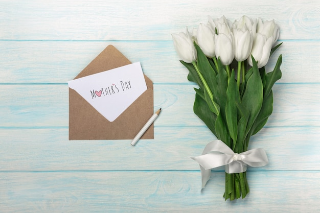 A bouquet of white tulips with love note and envelope on blue wooden boards . mother's day