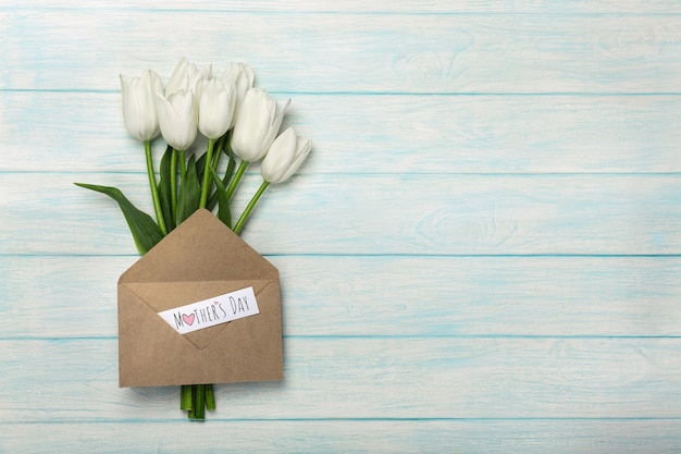 A bouquet of white tulips with a love note and envelope on blue wooden boards . mother's day
