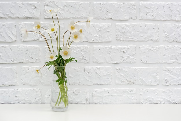 Bouquet of white wildflowers in vase on table white brick wall copyspace