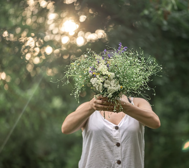 A bouquet of wild flowers in the hands of a girl on a blurred background in the forest.
