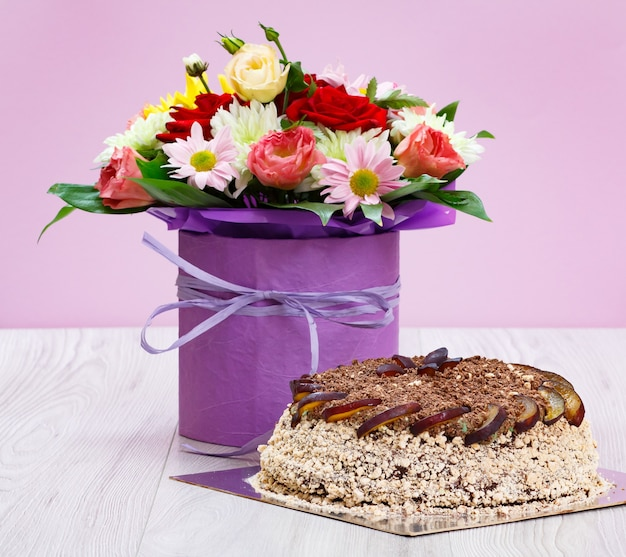 Bouquet of wildflowers and a chocolate cake on the wooden boards