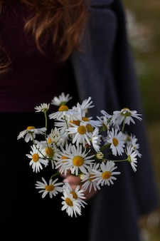 Bouquet of wildflowers daisies in female hands. spring nature. back to basics