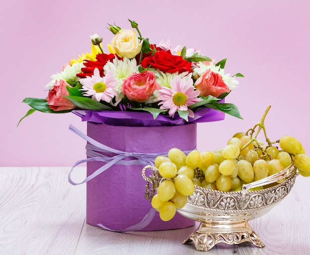 Bouquet of wildflowers and grapes in a metal vase on the wooden boards