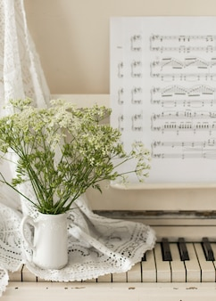 Bouquet wildflowers on white piano with notes. retro photo