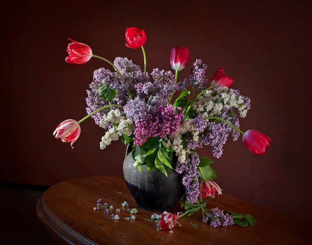 Bouquet with blooming branches of lilac and tulips in a clay jug on a wooden table.