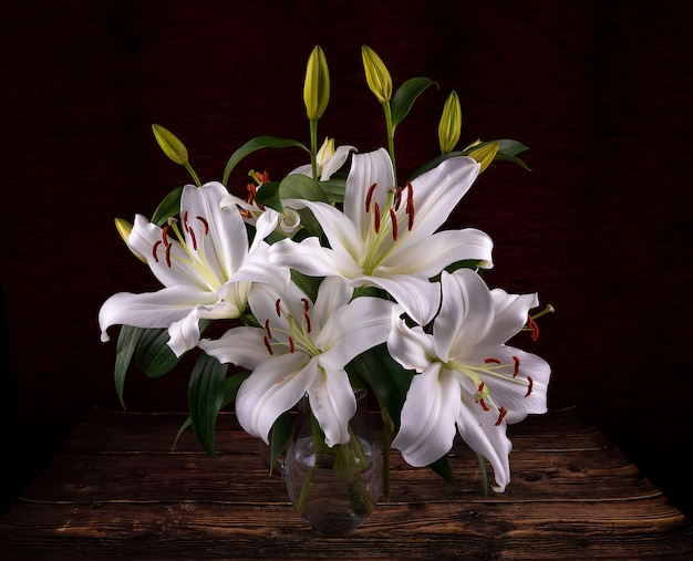 어두운 배경에 꽃병에 피는 흰 백합 꽃 봉 오리와 꽃다발