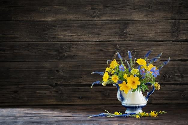 木製のテーブルにティーポットの青と黄色の花と花束