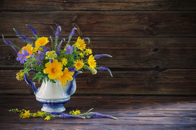 Букет с синими и желтыми цветами в чайнике на деревянном столе
