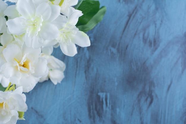 파란색에 자연적인 흰색 장미 배열이 있는 꽃다발.