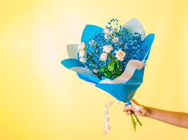黄色の背景に黄色いバラと小さな青い花を手にした花束。女性への贈り物。休日。あなたのテキストのためのスペース。