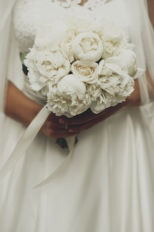 Bouquet of wonderful peonies in bride's tender arms