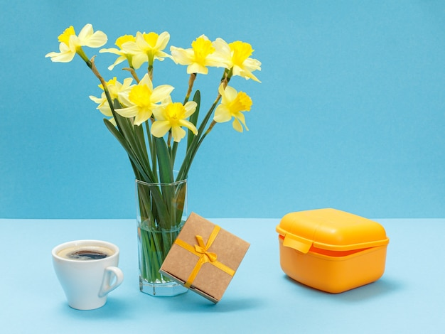 Bouquet of yellow daffodils in glass vase, a gift box, a cup of coffee and a lunch box on blue surface