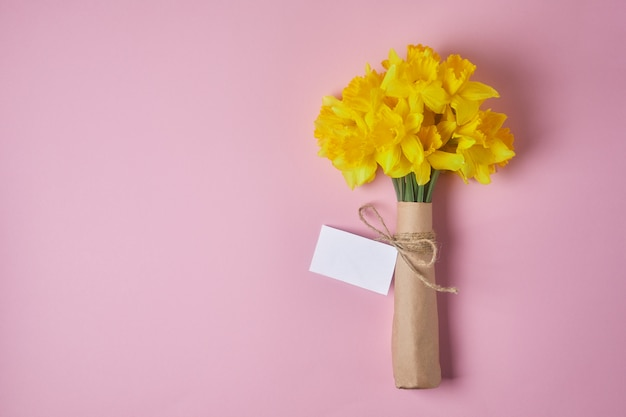Bouquet of yellow daffodils on a pink background