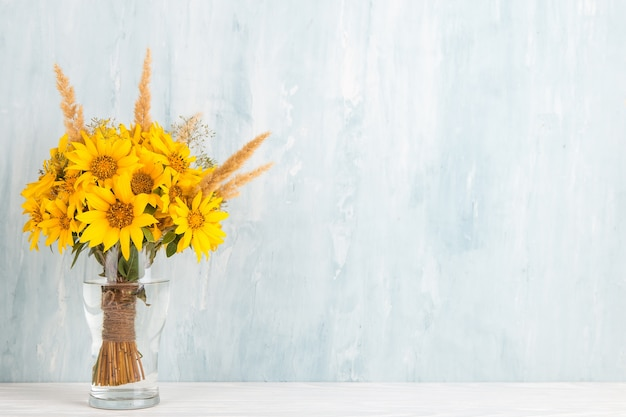 A bouquet of yellow flowers, sunflowers, in a glass vase on blue. copy space.