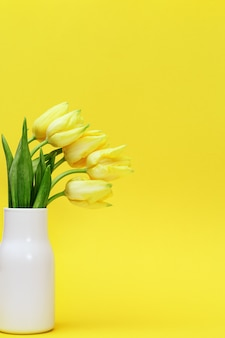 Bouquet of yellow flowers tulip in small ceramic vase on yellow background. natural spring flowers.
