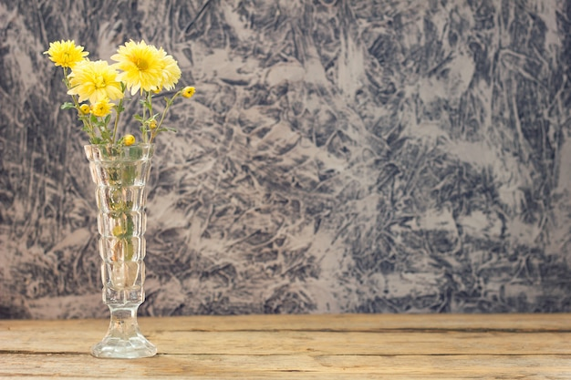 Bouquet of yellow flowers with a book on a beautiful wooden background with a copy of space