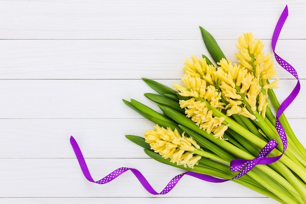 Bouquet of yellow hyacinths decorated with purple ribbon.