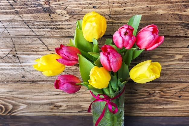 Bouquet of yellow and pink tulips on a wooden .