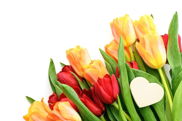 Bouquet of yellow and red tulips with a small heart isolated on white background. spring and summer backdrop. mother's day, easter and seasonal holiday
