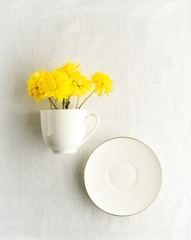 Bouquet of yellow spring flowers in white tea cup