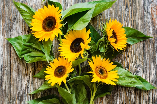 Bouquet of yellow sunflowers on vintage textured wooden table.