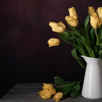 Bouquet of yellow tulip flowers in a vintage white jug on dark background