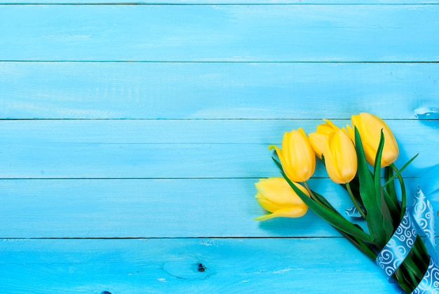 Bouquet of yellow tulips  on a blue wooden background