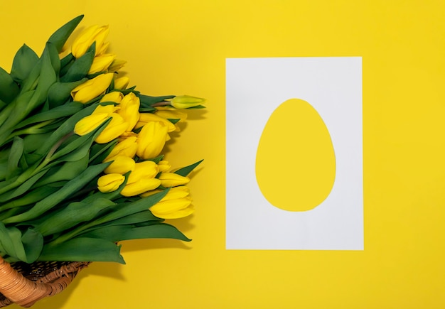 Bouquet of yellow tulips and card in the form of an easter egg.