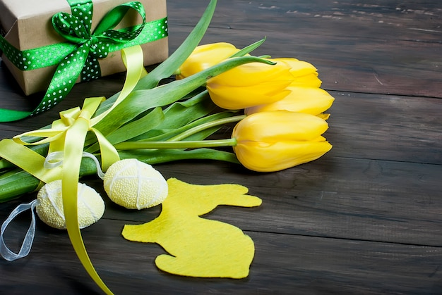 Bouquet of yellow tulips and chikken easter eggs with a blue ribbon on a wood